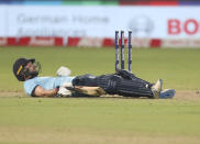 England's Mark Wood lies on the ground after his dismissal during the third One Day International cricket match between India and England at Maharashtra Cricket Association Stadium in Pune, India, Sunday, March 28, 2021. (AP Photo/Rafiq Maqbool)