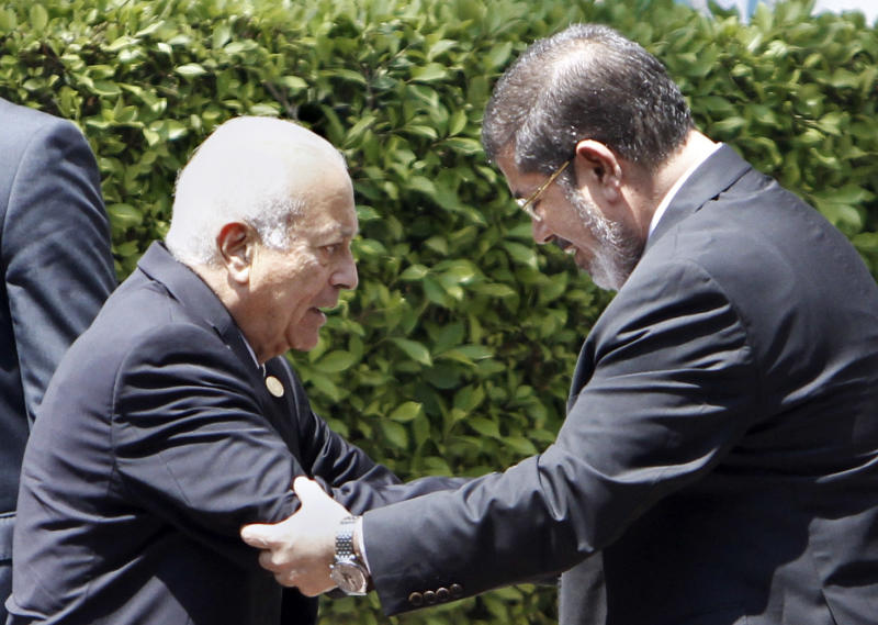 """Arab League Secretary-General Nabil Elaraby, left, greets Egyptian President Mohammed Morsi, as he leaves the Arab League headquarters in Cairo, Egypt, Wednesday, Sept. 5, 2012. Morsi says Syrian leader Bashar Assad must learn from """"recent history"""" and step down before it is too late. (AP Photo/Amr Nabil)"""
