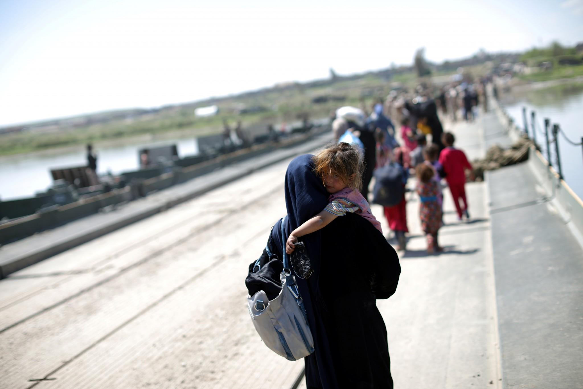 An Iraqi woman carries a girl across a pontoon bridge over the Tigris River south of Mosul, Iraq