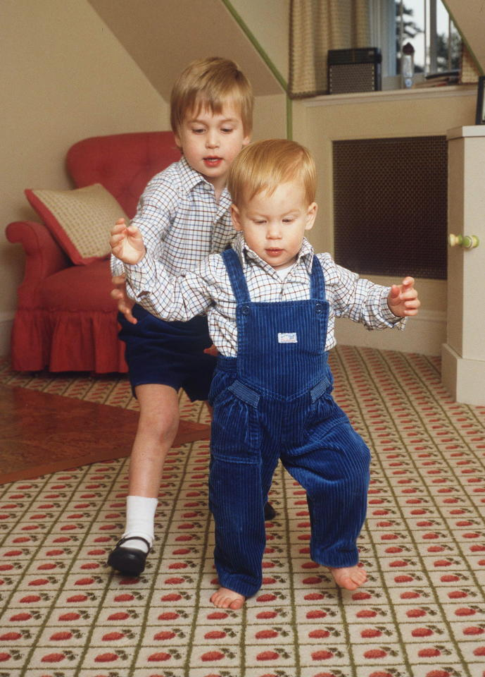 <p>Prince Harry takes his first steps with help from his older brother Prince William in the playroom of Kensington Palace on October 22, 1985. <em>[Photo: Getty]</em> </p>