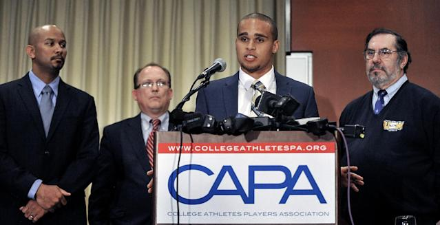 "Northwestern quarterback Kain Colter second from right, speaks while College Athletes Players Association president Ramogi Huma left, United Steel Workers National Political Director Tim Waters second from left, and United Steel Workers president Leo Gerard right, look on during a news conference in Chicago, Tuesday, Jan. 28, 2014. Calling the NCAA a ""dictatorship,"" a handful of Northwestern football players announced they are forming the first labor union for college athletes--one they hope will eventually represent players nationwide. (AP Photo/Paul Beaty)"