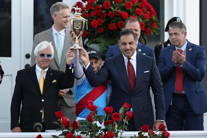 (L-R) Trainer Bob Baffert, jockey John Velazquez, and owner Amr Zedan of Medina Spirit raise the trophy after winning the 147th running of the Kentucky Derby at Churchill Downs on May 1, 2021 in Louisville, Kentucky. / Credit: Getty Images