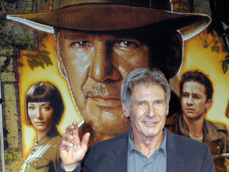 <p>Indiana Jones looms over Harrison Ford at the Japanese premiere of 'Indiana Jones and the Kingdom of the Crystal Skull' in 2008.</p> (AFP via Getty Images)