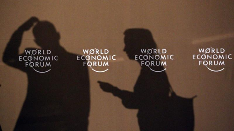 Shadows of participants of the World Economic Forum are seen on a wall in Davos