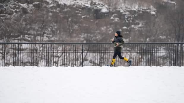 A woman jogs in a quiet park in Ottawa, Ont., in January 2021. Vigorous outdoor exercise during cold winter months can constrict and irritate lungs and cause a chronic cough.  (CBC - image credit)