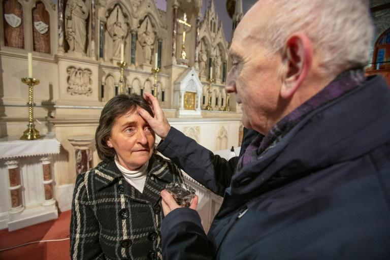 Father Brian Brady puts ashes on the forehead of Church Sacristan Breege McEleney for Ash Wednesday at St Mary's Church in Clonmany, County Donegal