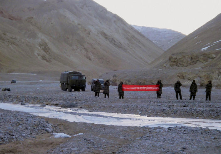 """FILE - In this Sunday, May 5, 2013 photo, Chinese troops hold a banner which reads: """"You've crossed the border, please go back,"""" in Ladakh, India. While the recent troop standoff in a remote Himalayan desert spotlights a long-running border dispute between China and India, the two emerging giants are engaged in a rivalry for global influence that spreads much farther afield. (AP Photo/File) INDIA OUT"""