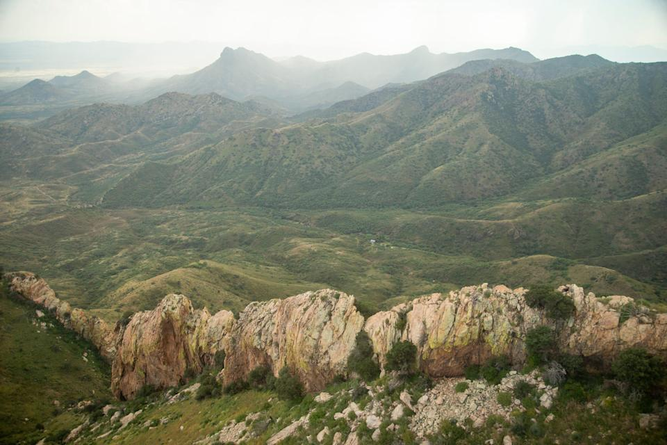 Smuggling routes pass through the rugged Baboquivari mountains, southwest of Tucson, Ariz. Rain makes the otherwise brown desert green with growth.