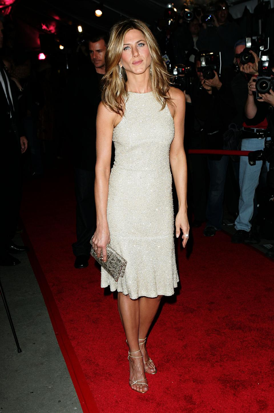 """Aniston shimmered in a sparkling cream and gold dress that showed off her tanned physique at the 2005 premiere of her film, """"Derailed."""" (Photo by James Devaney/WireImage)"""