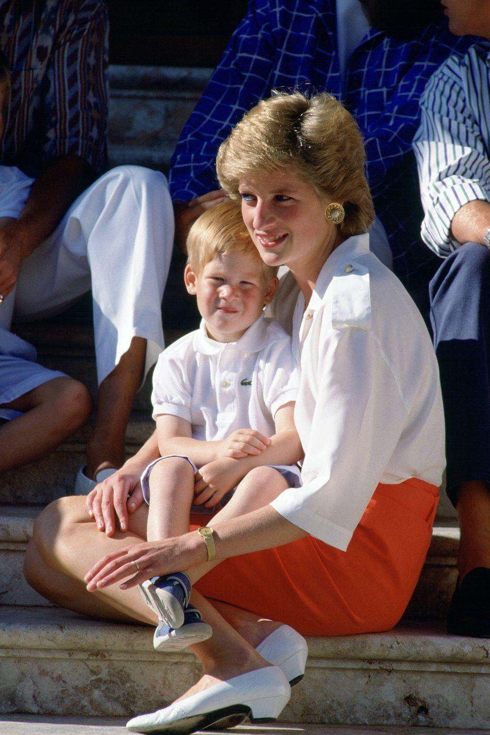 <p>Harry sits on Princess Diana's lap on the steps Marivent Palace during a family vacation.</p>
