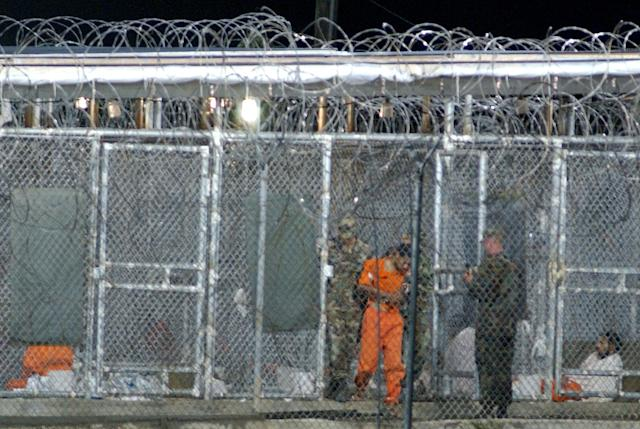 403051 02: A detainee is removed from his cell by guards March 28, 2002 at Camp Xray in Guantanamo Bay, Cuba. Over 300 detainees continue to be held at the camp as officials in Washington, DC are busy setting up military tribunals that will decide many of the prisoners'' fates. (Photo by Chris Hondros/Getty Images)