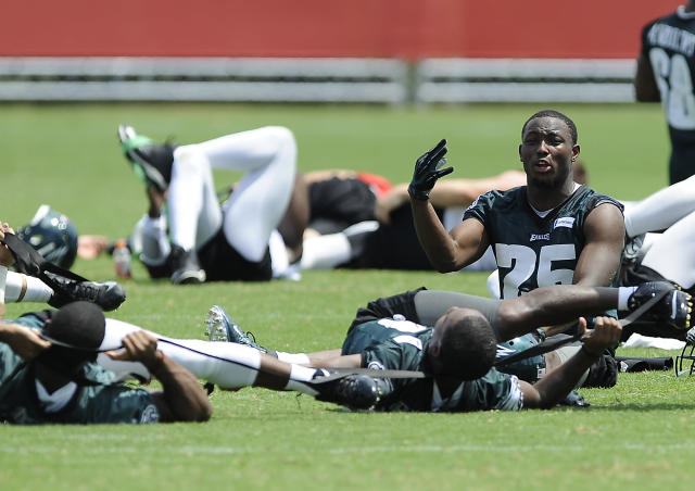 Philadelphia Eagles' LeSean McCoy, right, talks to Darren Sproles, bottom, while they stretch during NFL football training camp on Sunday, July 27, 2014, in Philadelphia. (AP Photo/Michael Perez)