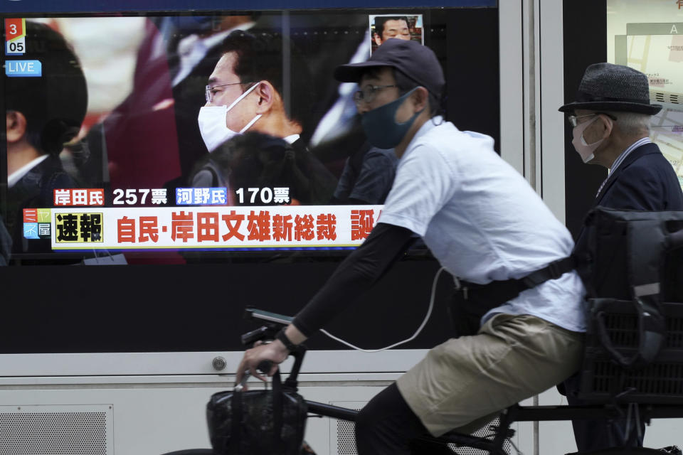 """A man rides a bicycle past a public TV showing Fumio Kishida, former foreign minister, during the Liberal Democratic Party's presidential election Wednesday, Sept. 29, 2021, in Tokyo. Kishida has won the governing party leadership election and is set to become the next prime minister. The Japanese letters read: """"Fumio Kishida new LDP president."""" (AP Photo/Eugene Hoshiko)"""