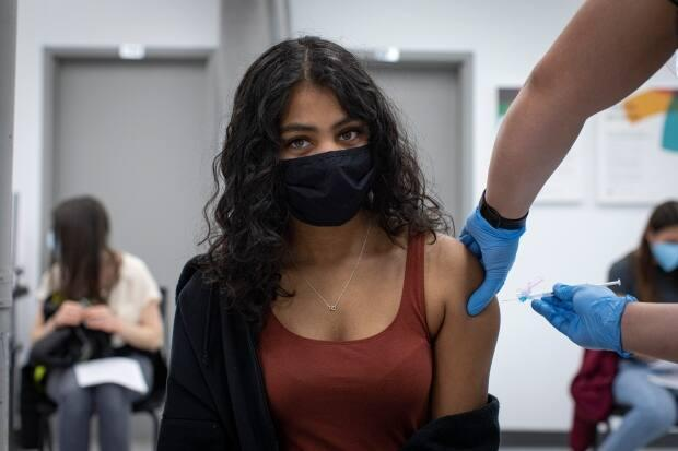 Menusha Manokumar, 20, gets her first dose of a COVID-19 vaccine at a pop-up clinic at Yorkgate Mall. Similar clinics are the only current option for adults aged 18 to 50 in hot-spot neighbourhoods. (Evan Mitsui/CBC - image credit)
