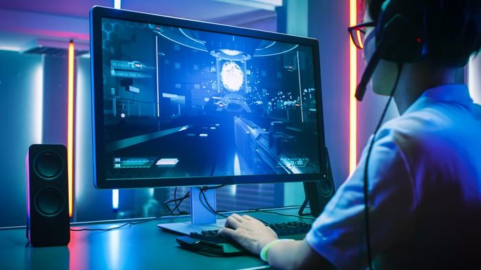 A person wearing a headset and playing a video game on a PC