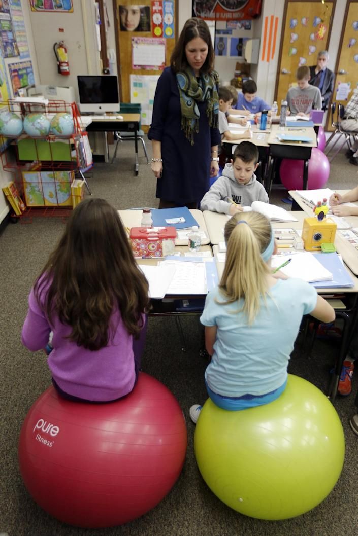 Robbi Giuliano teaches her fifth grade class as they sit on yoga balls at Westtown-Thornbury Elementary School Monday, Feb. 4, 2013, in West Chester, Pa. Replacing stationary seats with inflatable bouncers has raised productivity in her fifth-graders at Westtown-Thornbury Elementary School. (AP Photo/Matt Rourke)