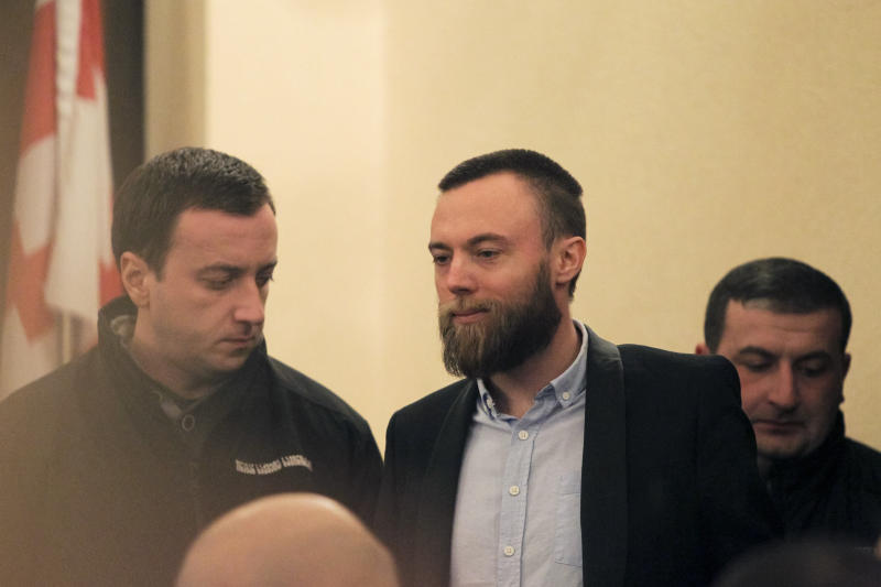 British Jack Shepherd, center, arrives for a court session in Tbilisi, Georgia, Friday, Jan. 25, 2019. A court in the ex-Soviet republic of Georgia has ruled to keep Shepherd a fugitive British man for three months behind bars pending possible extradition. (AP Photo/Shakh Aivazov)