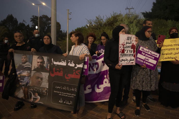 """Protesters hold signs and chant slogans during a demonstration against violence near the house of Public Security Minister Omer Barlev in the central Israeli town of Kokhav Ya'ir, Saturday, Sept. 25, 2021. Arab citizens of Israel are seeking to raise awareness about the spiraling rate of violent crime in their communities under the hashtag """"Arab lives matter,"""" but unlike a similar campaign in the United States, they are calling for more policing, not less. Arabic reads: """"Cry of anger, enough killing."""" (AP Photo/Sebastian Scheiner)"""