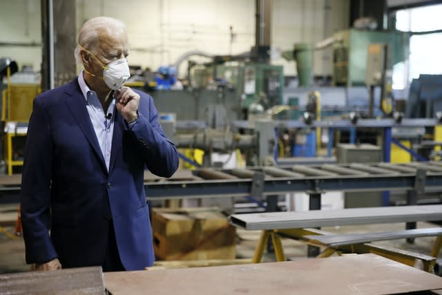 Joe Biden adjusts his mask during a tour of a factory in Pennsylvania (Matt Slocum/AP)