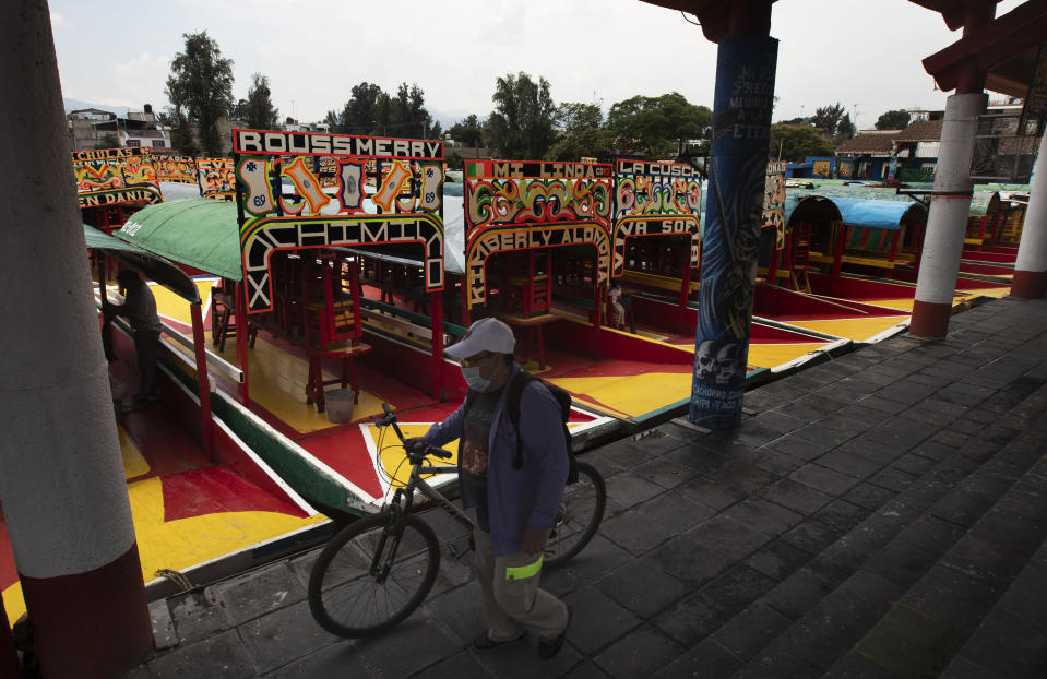 A man, wearing a protective face mask, walks his bicycle past a row of painted wooden boats known as trajineras, popular with tourists that ply the water canals in the Xochimilco district of Mexico City, during a reopening of activities after a six-month pause due to the COVID-19 pandemic. (AP Photo/Marco Ugarte)