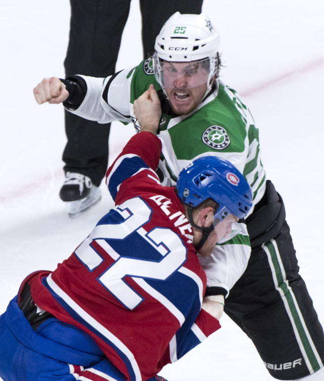 Dallas Stars right wing Brett Ritchie (25) and Montreal Canadiens defenseman Karl Alzner (22) square off during the second period of an NHL hockey game in Montreal on Tuesday, March 13, 2018. (Paul Chiasson/The Canadian Press via AP)