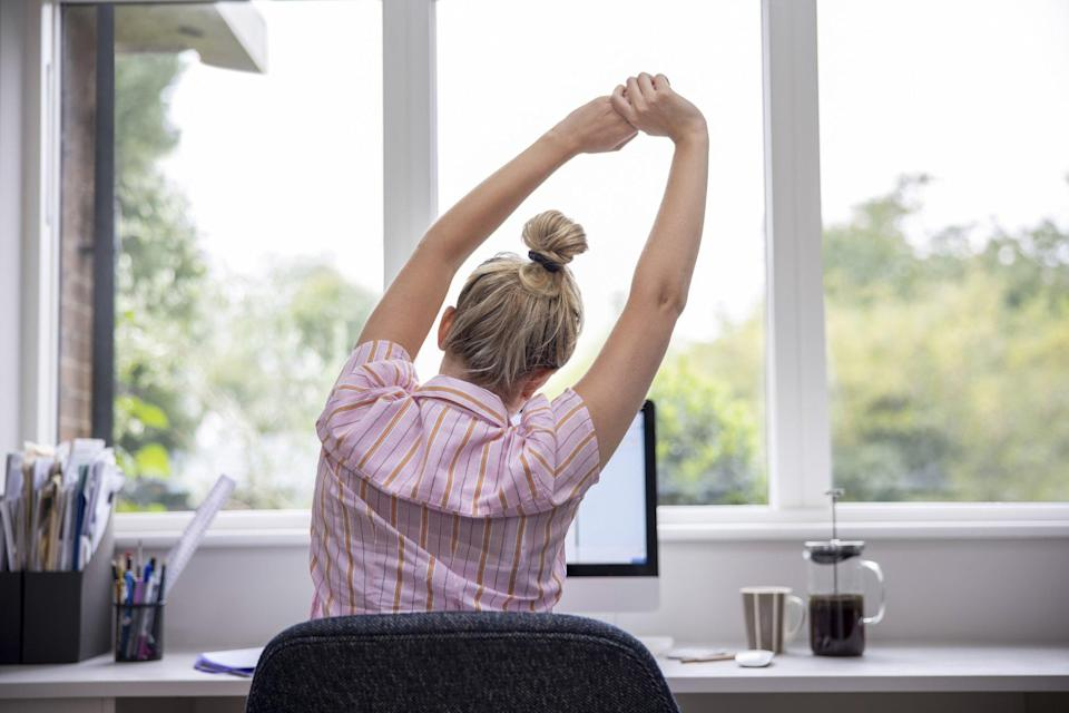 Rear View Of Woman Working From Home On Computer In Home Office Stretching At Desk
