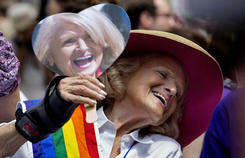 Edith Windsor, the 84-year-old woman at the center of the U.S. Supreme Court decision granting gay couples federal marriage benefits, smiles as she cools herself with a fan showing her image during the gay pride march in New York Sunday, June 30, 2013. (AP Photo/Craig Ruttle)