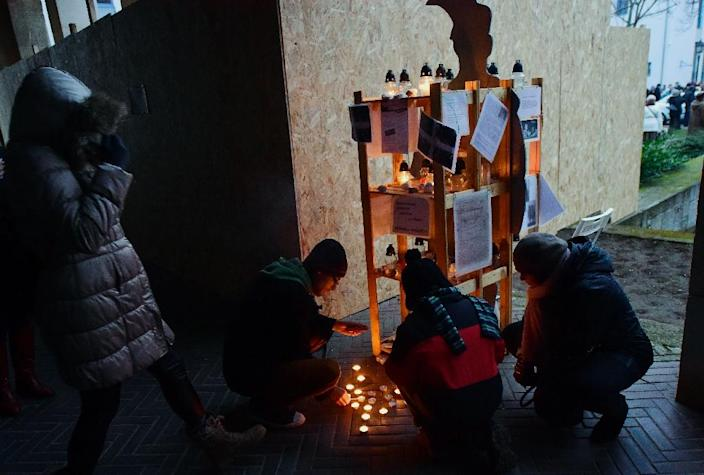 Young people light candles at Bartok square in Szekesfehervar town, southwest of Budapest, on December 13, 2015, as a protest beside the covered base of a planned statue in honor of Balint Homan (AFP Photo/Attila Kisbenedek)