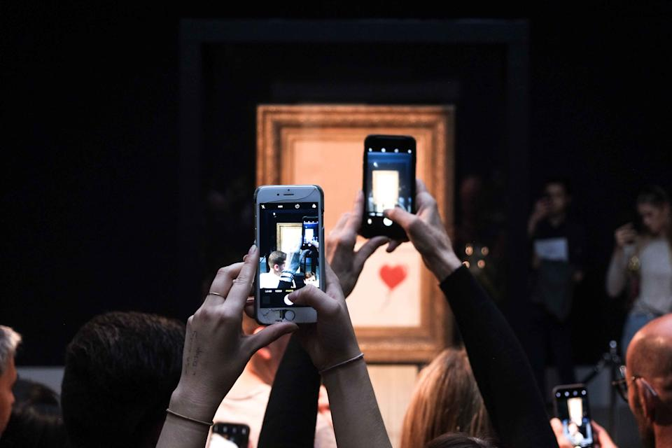 Visitors view Banksy's artwork tilted Love is in the Bin - previously known as - Girl with Balloon at Sotheby's Auction House in London, UK on October 13, 2018. (Photo by Claire Doherty/Sipa USA)