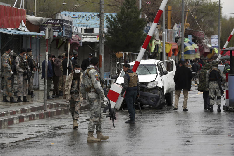 Afghan security forces inspect the site of a bomb explosion near a damaged vehicle in Kabul, Afghanistan, Monday, March 30, 2020.  A sticky bomb attached to the vehicle detonated, according to Firdaus Faramraz, spokesman for the Kabul police chief. (AP Photo/Rahmat Gul)