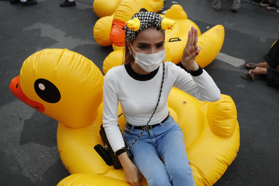 An anti-government protester flashes the three finger protest gesture while seated on an inflatable yellow duck, a symbol of the protest movement, during a rally Wednesday, Dec. 2, 2020 in Bangkok, Thailand. Thailand's highest court Wednesday acquitted Prime Minister Prayuth Chan-ocha of breaching ethics clauses in the country's constitution, allowing him to stay in his job. (AP Photo/Sakchai Lalit)