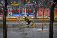 A man wears a face mask as he rides a bicycle along a street during a snowfall in Beijing, Friday, Feb. 14, 2020. China on Friday reported another sharp rise in the number of people infected with a new virus, as the death toll neared 1,400. (AP Photo/Mark Schiefelbein)