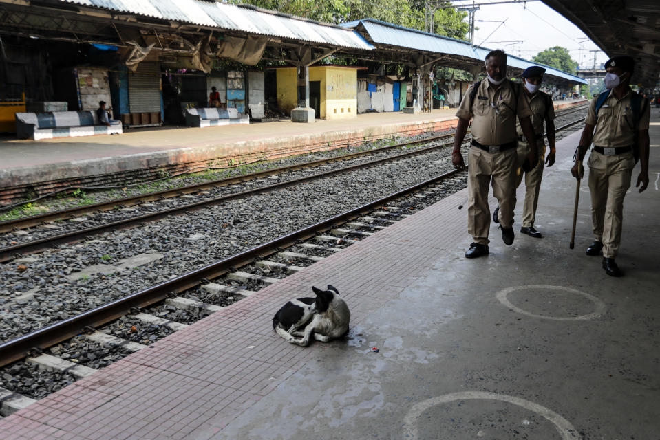 Railway Protection Force personnel patrol a deserted local railway platform as local trains were suspended due to the coronavirus pandemic, in Kolkata, India, Saturday, Oct. 10, 2020. India's total coronavirus positive cases near 7 million with another 73,272 infections reported in the past 24 hours. The Health Ministry on Saturday put the total positive caseload at 6.97 million, second to 7.66 million infections registered in the worst-hit United States. (AP Photo/Bikas Das)