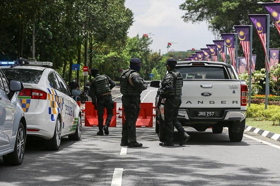 Police personnel stand guard at the road leading to Parliament in Kuala Lumpur March 27, 2021.