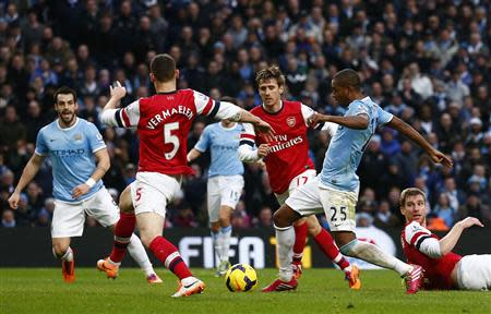 Manchester City's Fernandinho (2nd R) kicks to score his second goal against Arsenal during their English Premier League soccer match at the Etihad stadium in Manchester, northern England, December 14, 2013. REUTERS/Darren Staples