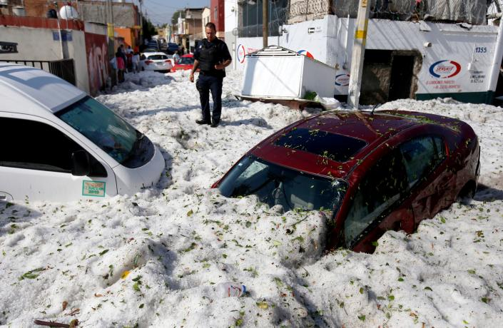 A policeman near vehicles buried in hail in Guadalajara, Mexico, on June 30. (Photo: Ulisies Ruiz/AFP/Getty Images)