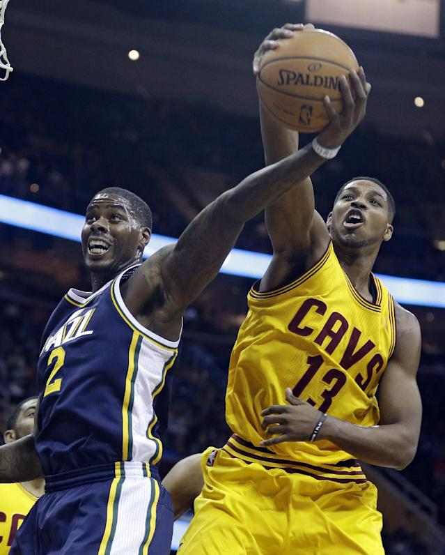 Utah Jazz's Marvin Williams (2) and Cleveland Cavaliers' Tristan Thompson (13), from Canada, battle for a rebound during the first quarter of an NBA basketball game on Friday, Feb. 28, 2014, in Cleveland. (AP Photo/Tony Dejak)