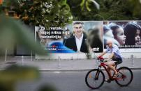 A man rides a bike past a banner advertising the campaign of Croatian Prime Minister and the leader of the centre-right Croatian Democratic Union (HDZ) Andrej Plenkovic in Zagreb