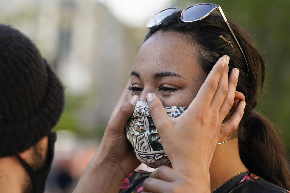 Joseph Ravago wipes tears from the eyes of Kamaile Elderts on Tuesday, April 20, 2021, in Washington, after the verdict in Minneapolis, in the murder trial against former Minneapolis police officer Derek Chauvin was announced. (AP Photo/Alex Brandon)