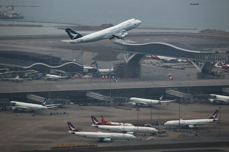 A Cathay Pacific Airways aircraft takes off at the Hong Kong International Airport on March 6, 2020. Hong Kong airline Cathay Pacific Airways on Wednesday, Oct. 21, 2020, said it would cut 8,500 jobs and shut down its regional airline unit in a corporate restructuring, as it grapples with the plunge in air travel due to the pandemic. (AP Photo/Kin Cheung)