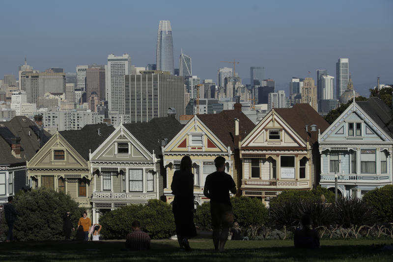 """FILE - In this Feb. 26, 2020, file photo, visitors look toward the """"Painted Ladies,"""" a row of historical Victorian homes, in front of the San Francisco skyline from Alamo Square Park in San Francisco. An estimate released Friday, May 1, 2020, by the California Department of Finance said that more people are leaving California than moving in, evidence of the toll the state's housing crisis is taking as the world's fifth largest economy inches toward 40 million people. (AP Photo/Jeff Chiu, File)"""