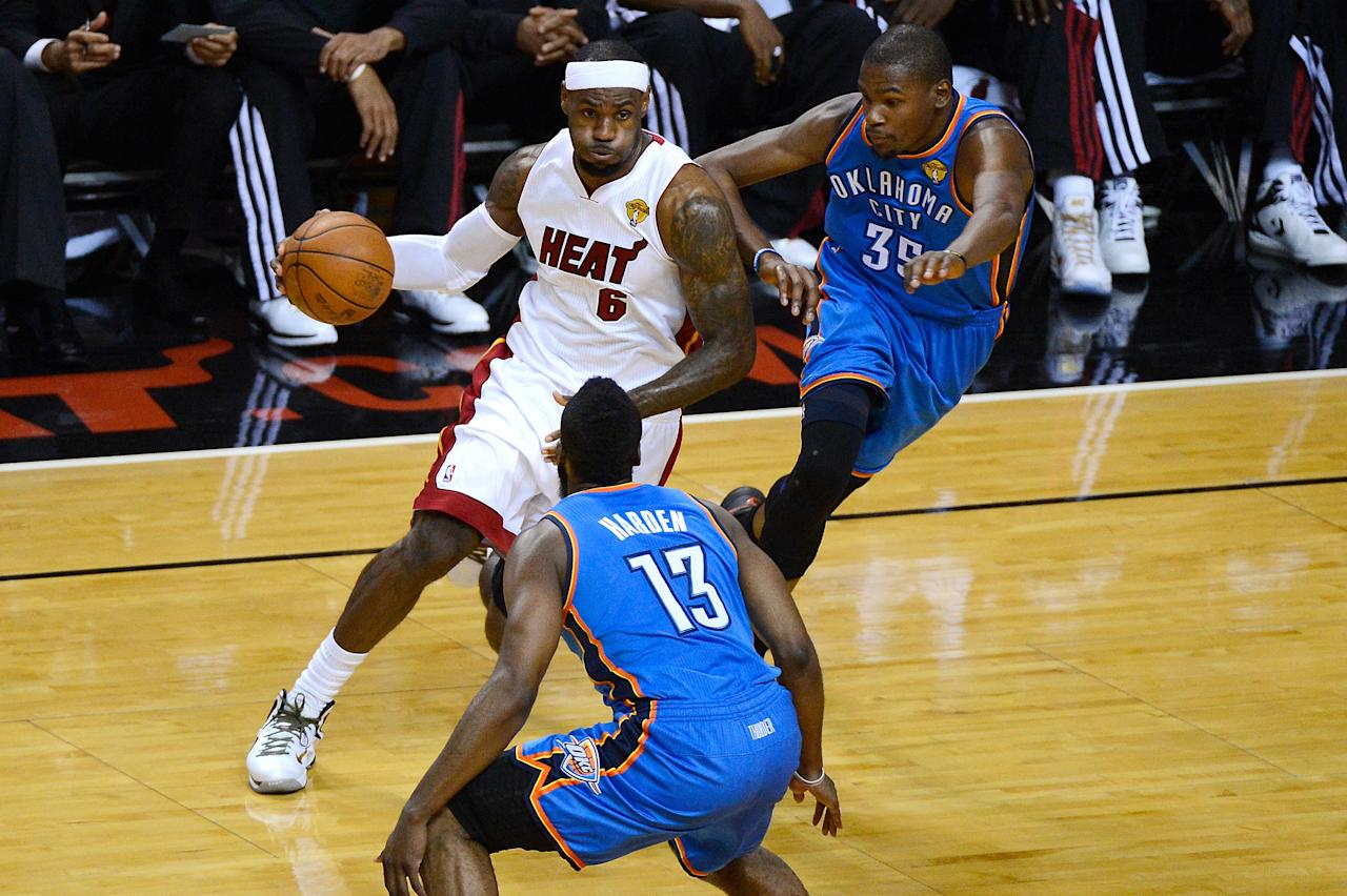 MIAMI, FL - JUNE 17:  LeBron James #6 of the Miami Heat drives in the first quarter against James Harden #13 and Kevin Durant #35 of the Oklahoma City Thunder in Game Three of the 2012 NBA Finals on June 17, 2012 at American Airlines Arena in Miami, Florida.  NOTE TO USER: User expressly acknowledges and agrees that, by downloading and or using this photograph, User is consenting to the terms and conditions of the Getty Images License Agreement.  (Photo by Ronald Martinez/Getty Images)