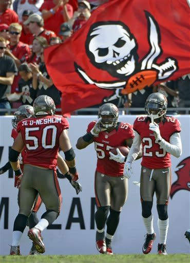 Tampa Bay Buccaneers linebacker Adam Hayward (57) celebrates with teammates defensive end Daniel Te'o-Nesheim (50) and defensive back Myron Lewis (23) after returning a blocked punt for a touchdown during the second quarter of an NFL football game Sunday, Nov. 11, 2012, in Tampa, Fla. (AP Photo/Phelan M. Ebenhack)