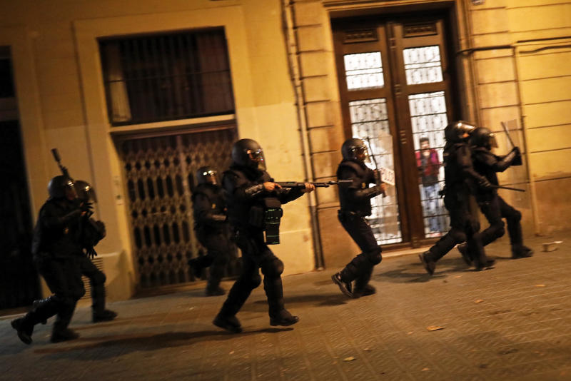 Police in riot gear moves after protestors during clashes in Barcelona, Spain, Wednesday, Oct. 16, 2019. Spain's government said Wednesday it would do whatever it takes to stamp out violence in Catalonia, where clashes between regional independence supporters and police have injured more than 200 people in two days. (AP Photo/Bernat Armangue)