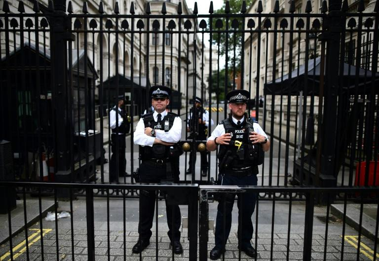 British police officers stand on duty outside the gated entrance to Downing Street in central London on June 28, 2016