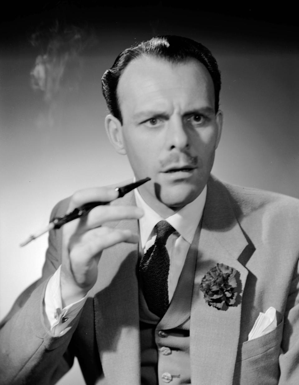 1951:  English actor-comedian Terry Thomas (1911 - 1990), real name Thomas Terry Hoar-Stevens, smoking a cigarette in a long holder.  (Photo by Denis De Marney/Getty Images)