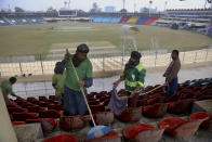 Pakistani workers clean an enclosure at Gaddafi stadium as preparation for the upcoming series against Bangladesh in Lahore, Pakistan, Tuesday, Jan. 21, 2020. Pakistan will play three Twenty20 series against Bangladesh, starting from Jan. 24, at Lahore. (AP Photo/K.M. Chaudary)