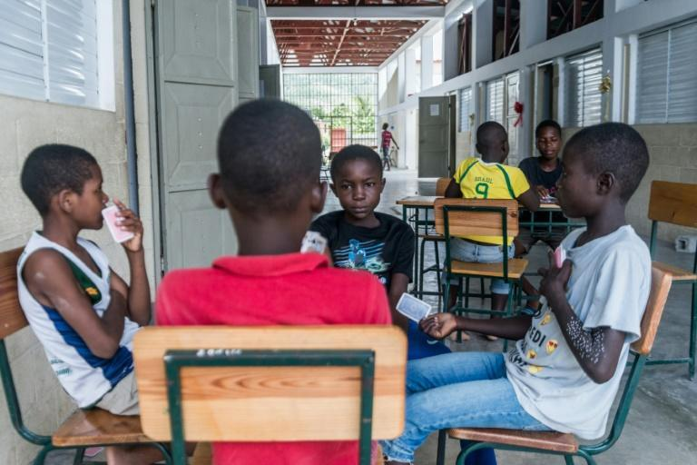 Children play cards at a school in the Haitian town of Chardonnieres that has been turned into a shelter for people left homeless by an August 14 earthquake (AFP/Reginald LOUISSAINT JR)
