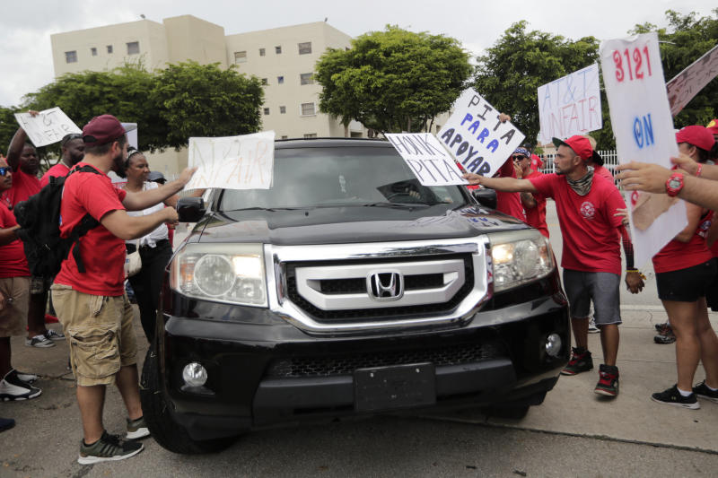 Members of the Communications Workers of America (CWA) surround a vehicle driving into an AT&T office as they walk a picket line, Monday, Aug. 26, 2019, in Miami. CWA union members in the southeast went on strike Friday over unfair labor practices by management during negotiations for a new contract. (AP Photo/Lynne Sladky)