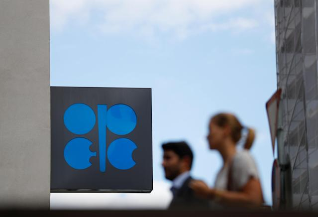 Two persons pass the logo of the Organization of the Petroleoum Exporting Countries (OPEC) in front of OPEC's headquarters in Vienna, Austria June 19, 2018. REUTERS/Leonhard Foeger
